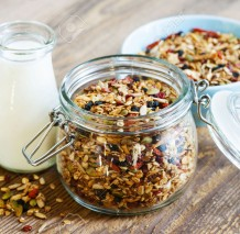 27768056-Homemade-granola-in-open-glass-jar-and-milk-or-yogurt-on-rustic-wooden-background-Stock-Photo
